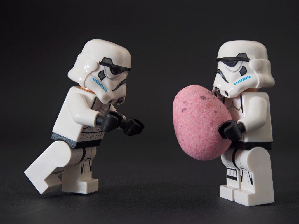 """Kaksi stormtrooper lego-ukkoa heittelmässä toisilleen munanmuotoista """"pallolla""""."""