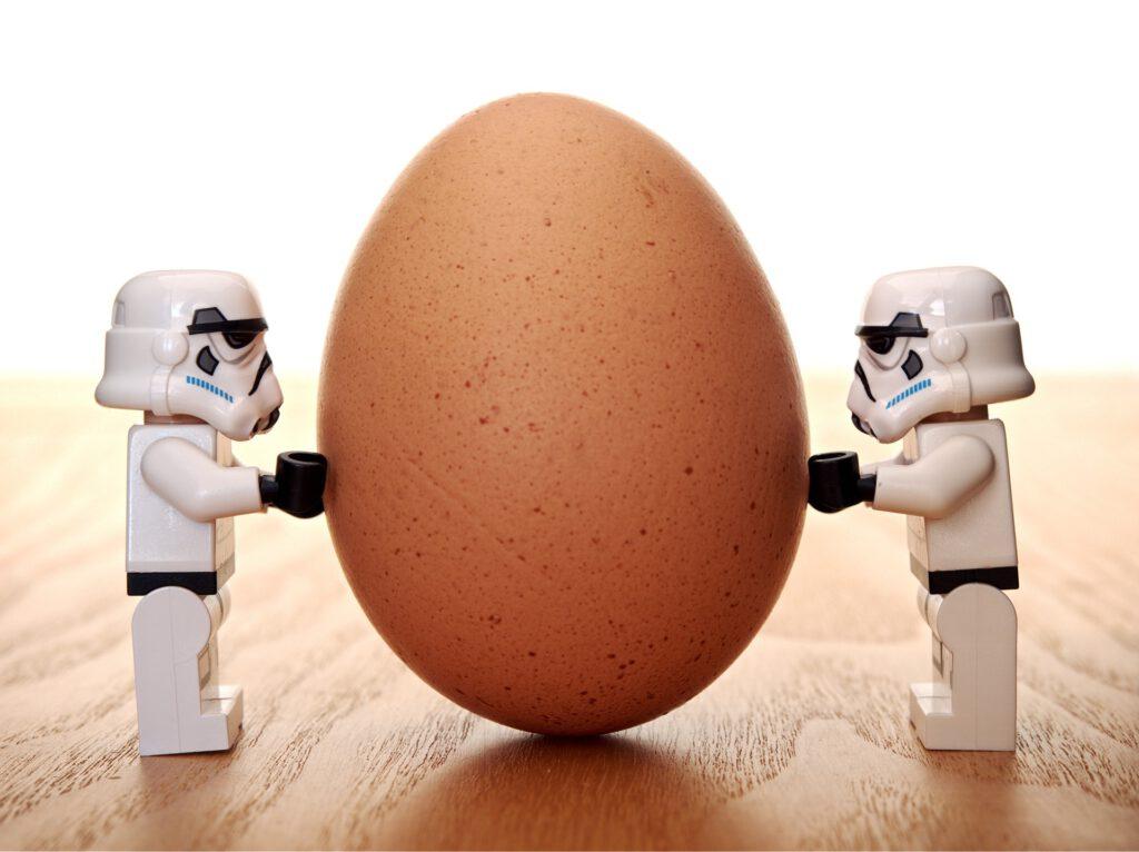 Kaksi stormtrooper-lego-ukkoa ova kasvokkain ja niiden välissä on kananmuna, jota vasten ne pitävät käsiään.